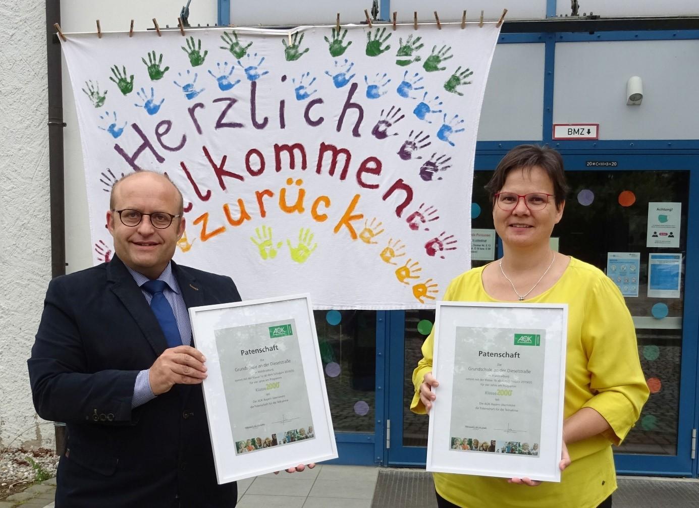Patenschaft besiegelt: AOK-Fachbereichsleiter Gesundheit Dieter Trost übergibt die Patenschaftsurkunden für die zwei Klassen an Schulleiterin Annette Gibis
